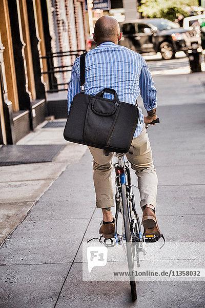 Businessman riding bike in street  rear view