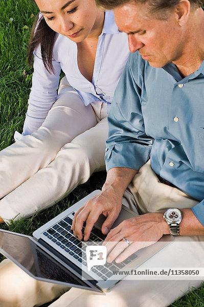 Geschäftsmann und -frau sitzen im Freien auf dem Rasen und benutzen einen Laptop