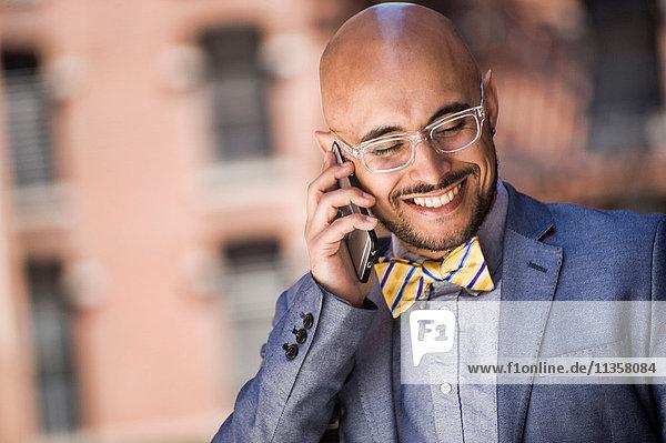 Geschäftsmann im Freien  benutzt Smartphone  lächelt
