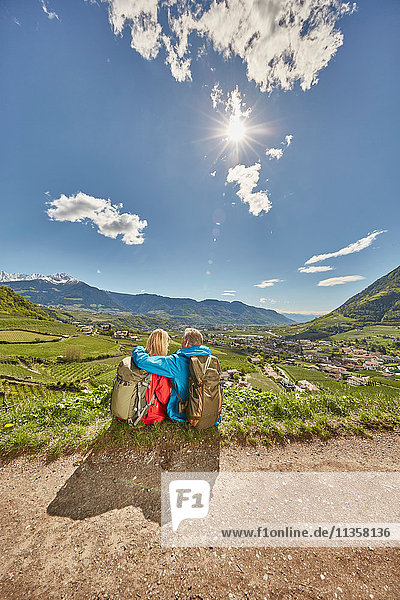 Mature couple sitting by roadside  looking at view  rear view  Meran  South Tyrol  Italy