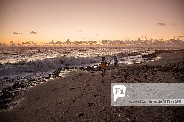 Junge und Schwester laufen bei Sonnenaufgang am Strand  Blowing Rocks Preserve  Jupiter Island  Florida  USA