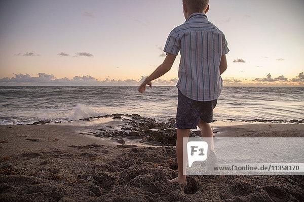 Rückansicht eines Jungen  der bei Sonnenaufgang am Strand spielt  Blowing Rocks Preserve  Jupiter Island  Florida  USA