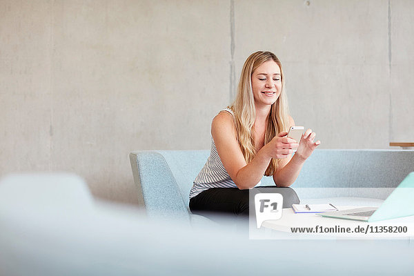 Junge Studentin sitzt auf einem Studienplatz-Sofa und liest Smartphone-Texte an einer Hochschule