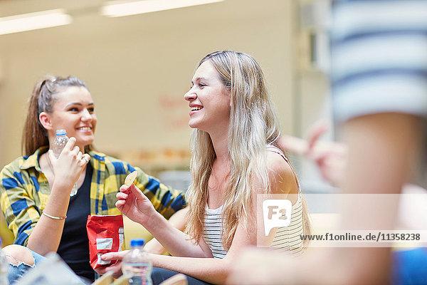 Zwei Studentinnen essen Chips in der Kantine der Hochschule