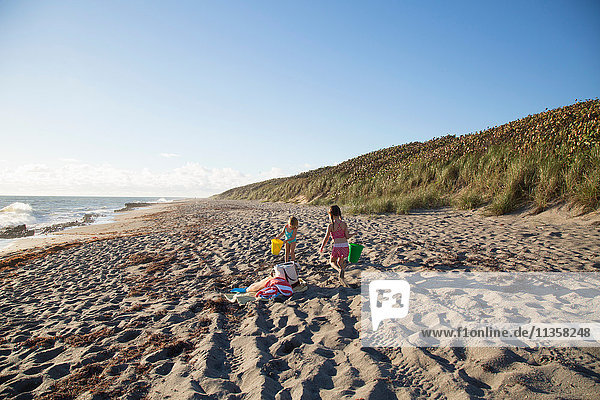 Two sisters playing with toy buckets on beach  Blowing Rocks Preserve  Jupiter Island  Florida  USA