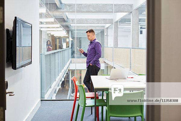 Männlicher Designer liest Smartphone-Update im Design-Studio