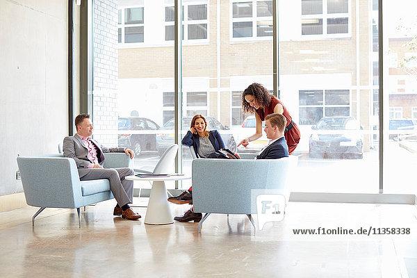 Geschäftsfrauen und -männer treffen sich auf Bürosofas