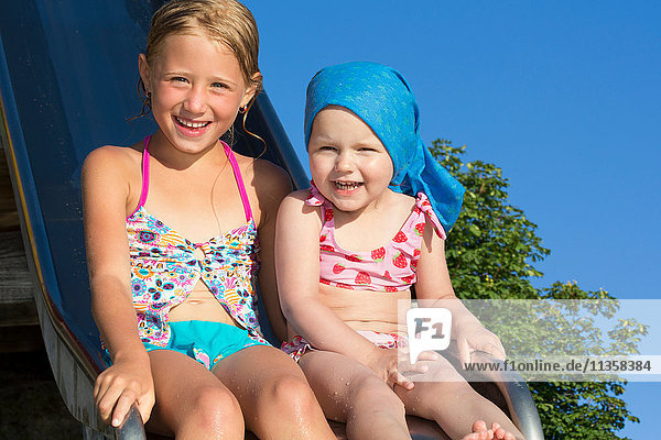 Portrait of girl and female toddler on water slide at Lake Seeoner See  Bavaria  Germany