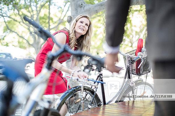 Geschäftsfrau schließt Fahrrad ab  während sie einen Geschäftsmann im Park trifft