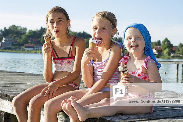 Zwei Schwestern und ein weibliches Kleinkind am Pier beim Essen von Eiswaffeln  Seeoner See  Bayern  Deutschland