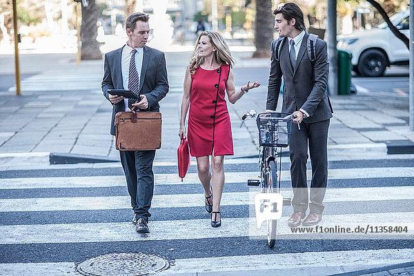 Geschäftsfrau und männliche Kollegen unterhalten sich beim Überqueren der Straße