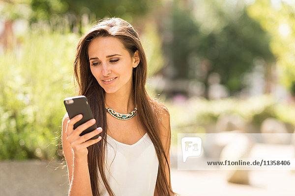 Junge Geschäftsfrau liest Smartphone-Text in der Stadt