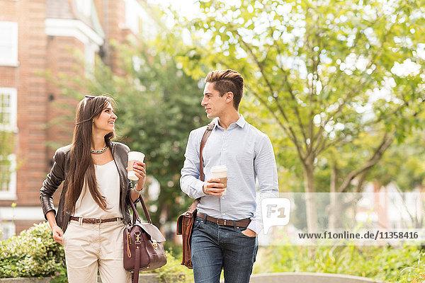 Junger Geschäftsmann und Geschäftsfrau beim Spazierengehen und Reden im Stadtpark