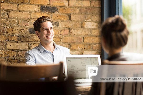 Junger Geschäftsmann und Frau mit Laptop und Gespräch im Cafe
