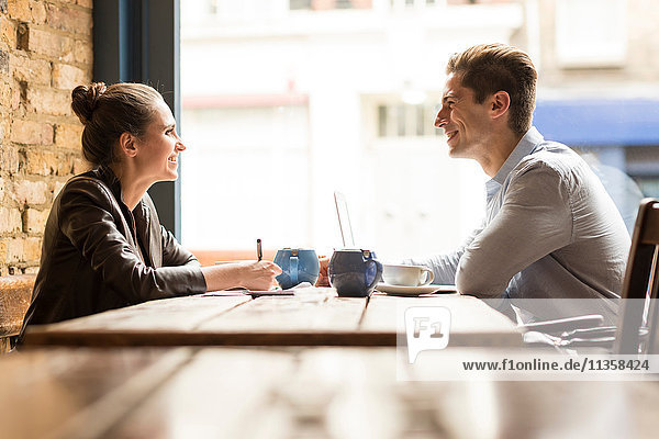 Young businessman and woman meeting in cafe