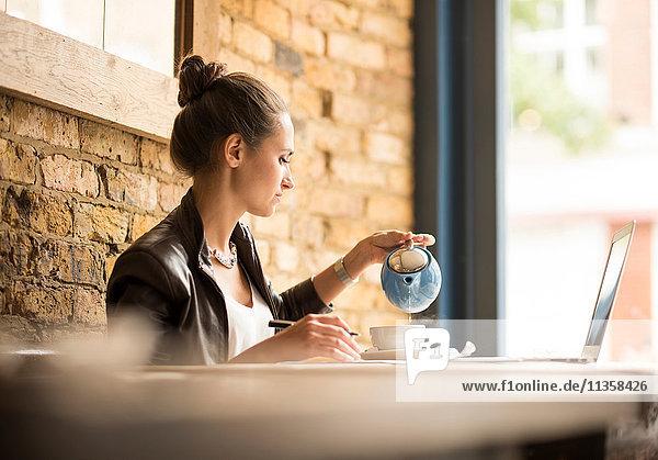 Junge Geschäftsfrau beim Tee trinken im Café