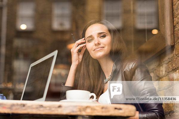 Schaufensterbild einer jungen Geschäftsfrau mit Laptop im Café