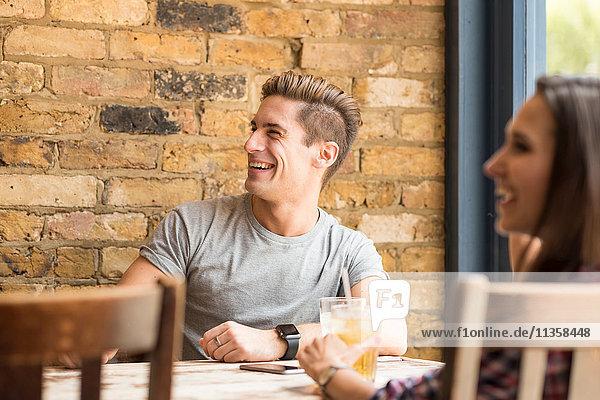 Junges Paar lacht und redet in der Bar