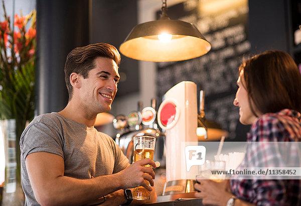 Junges Paar beim abendlichen Gespräch in der Bar