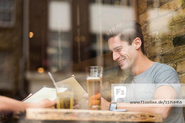 Fensteransicht des jungen Mannes beim Lesen der Speisekarte im Restaurant