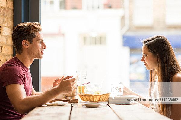 Junges Paar beim Essen im Restaurant im Gespräch