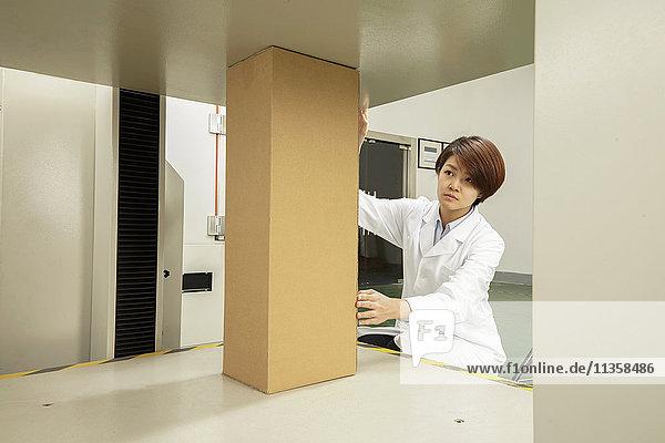 Weibliche Technikerin platziert Pappkarton auf Verpackungsmaschine in Druck- und Verpackungsfabrik  China
