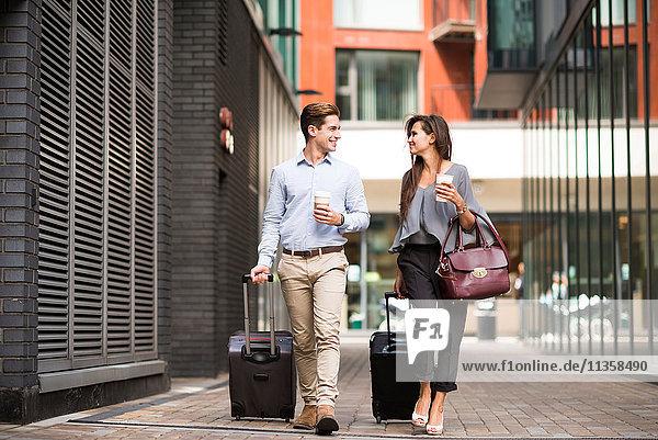 Junger Geschäftsmann und Frau mit fahrbaren Koffern beim Gehen und Sprechen  London  UK