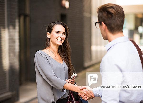 Junger Geschäftsmann und Geschäftsfrau beim Händeschütteln außerhalb des Büros  London  UK