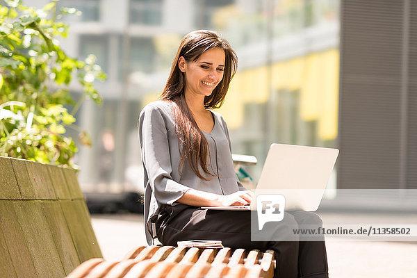 Geschäftsfrau beim Tippen am Laptop auf der Parkbank  London  UK
