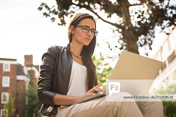 Geschäftsfrau beim Tippen auf dem Laptop in der Stadt  London  UK