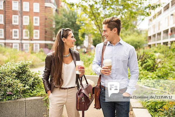 Geschäftsmann und -frau beim Spazierengehen und Reden in der Stadt  London  UK