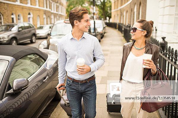 Geschäftsmann und Frau beim Gehen und Sprechen mit Rollkoffern  London  UK
