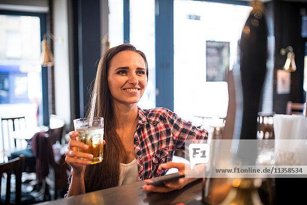 Junge Frau mit Smartphone in der Stadtbar