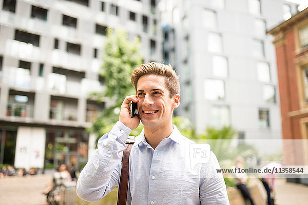 Young businessman talking on smartphone outside city office  London  UK