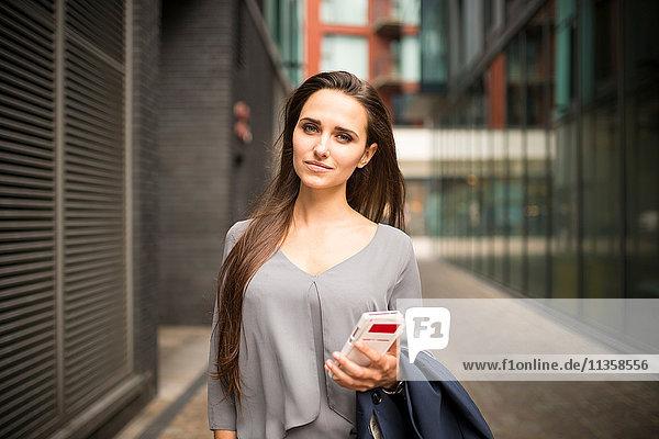 Junge Geschäftsfrau mit Smartphone außerhalb des Büros  London  UK