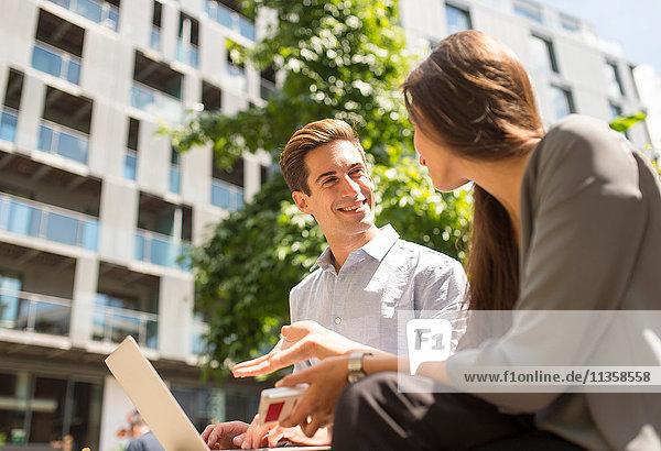 Junge Geschäftsfrau und Mann mit Laptop und Chat  London  UK