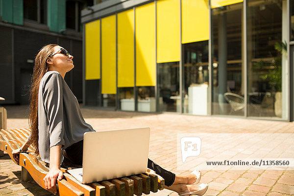 Junge Geschäftsfrau entspannt auf der Bank vor dem Büro  London  UK
