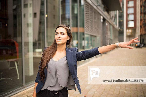 Junge Geschäftsfrau bei einem Taxi vor dem Büro  London  UK