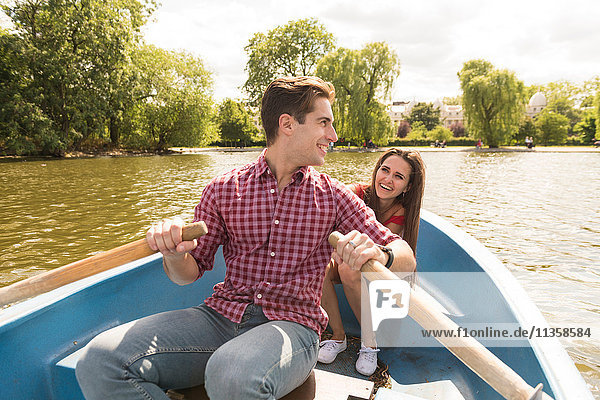 Young couple rowing on boating lake in Regents Park  London  UK