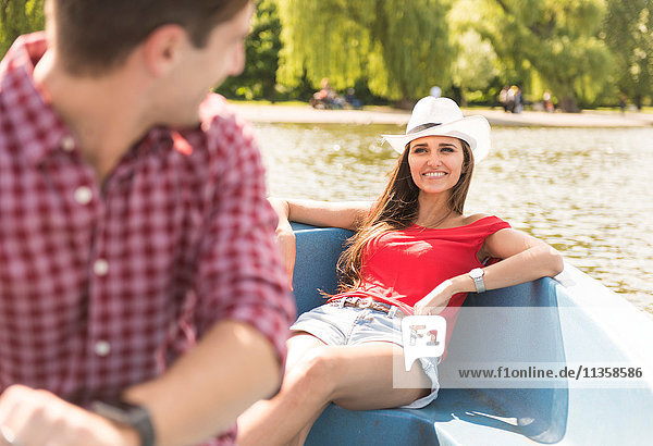 Happy young couple rowing on boating lake in Regents Park  London  UK