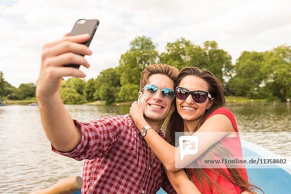 Young couple taking smartphone selfie in rowing boat in Regents Park  London  UK