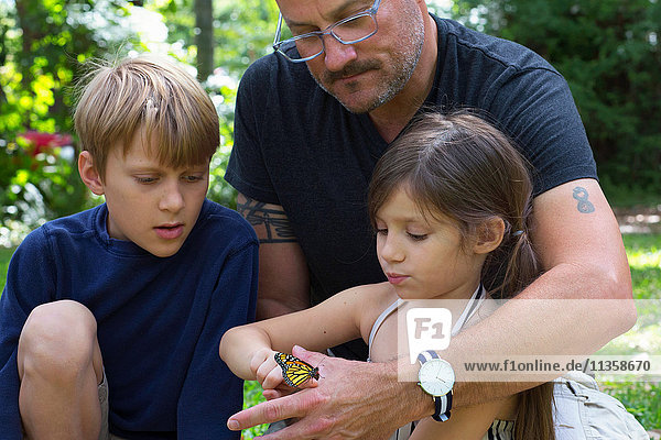 Father with son and daughter looking at monarch butterfly