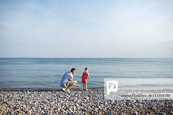 Mid adult man and daughter skimming stones at Lake Ontario  Oshawa  Canada