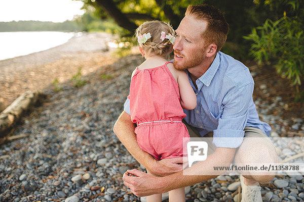 Mid adult man hugging daughter at Lake Ontario  Oshawa  Canada
