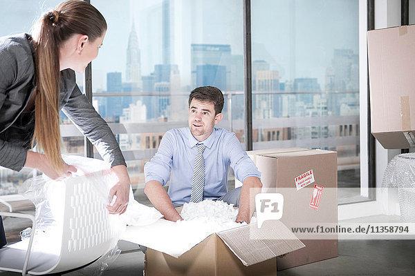 Geschäftsleute packen im Büro aus
