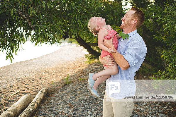 Mid adult man carrying and tickling daughter at Lake Ontario  Oshawa  Canada
