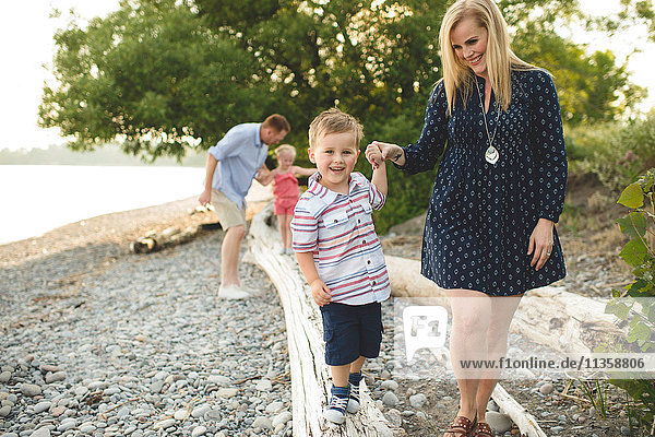 Mid adult woman holding hands with boy on tree trunk at Lake Ontario  Oshawa  Canada