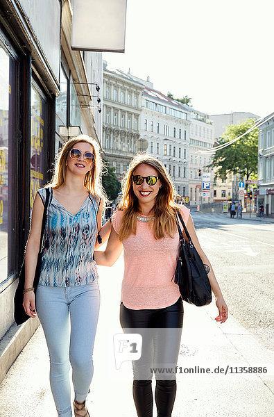 Zwei erwachsene Freundinnen spazieren auf dem Bürgersteig  Wien  Österreich