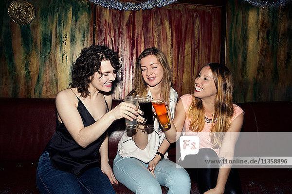 Three adult female friends raising a glass in bar