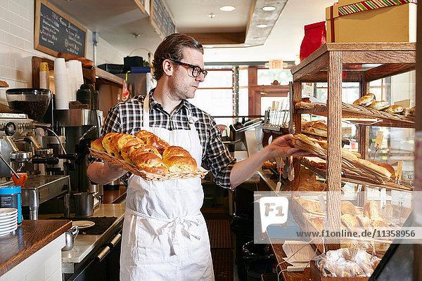 Männlicher Arbeiter in einer Bäckerei  der frisches Gebäck in eine Vitrine stellt